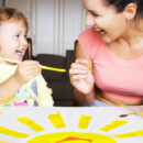 Childminder painting with child